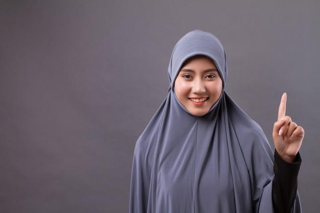 Mulher apontando para o número 1, modelo de mulher muçulmana asiática