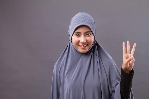 Mulher apontando para o número 3, modelo de mulher muçulmana asiática
