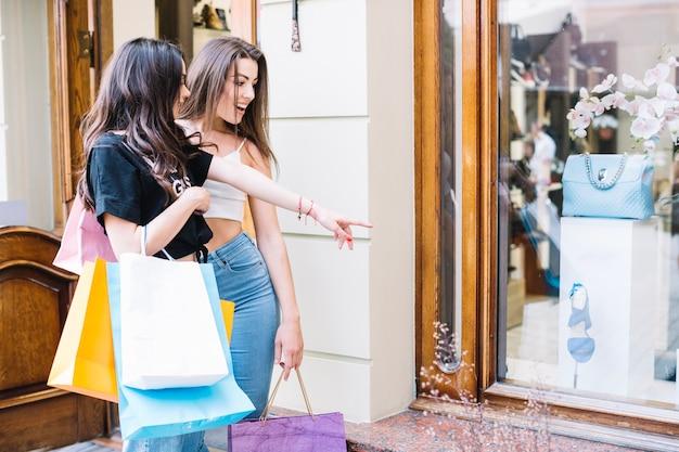 Mulher apontando para o saco atrás da loja