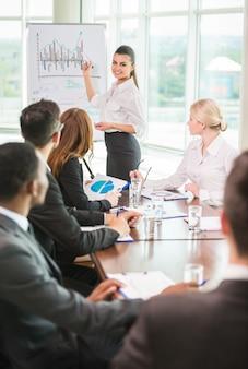 Mulher apontando para um gráfico crescente durante uma reunião.