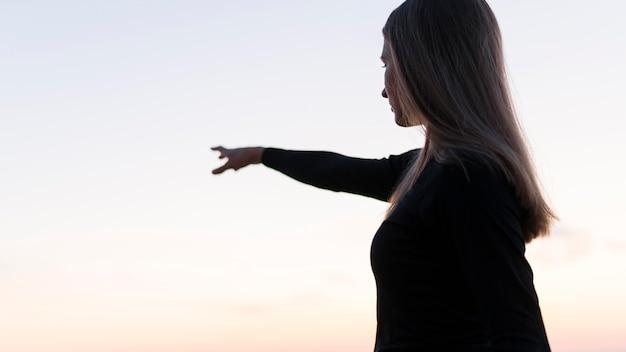 Mulher apontando para um lugar distante
