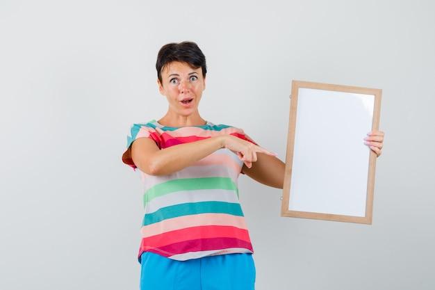 Mulher apontando para um quadro vazio em camiseta listrada, calça e parecendo espantado. vista frontal.