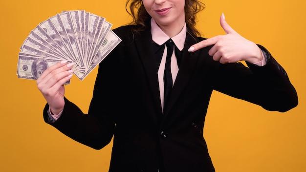 Mulher apontando para uma pilha de dinheiro com o dedo isolado em fundo amarelo.