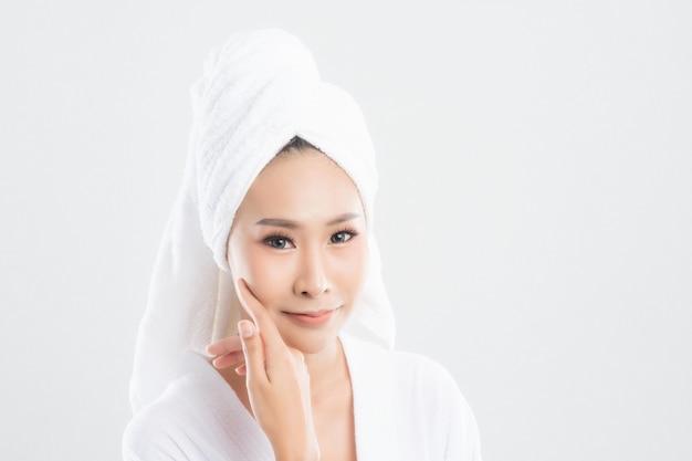 Mulher após o banho com uma pele limpa, perfeita, em fundo branco.