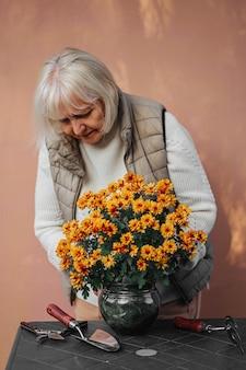 Mulher aposentada cuidando de flores decorativas em vasos. mulher idosa positiva em roupas casuais