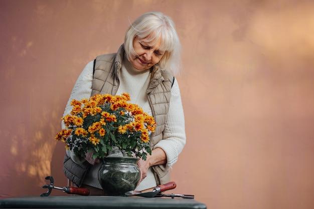 Mulher aposentada cuidando de flores decorativas em vasos. mulher idosa positiva