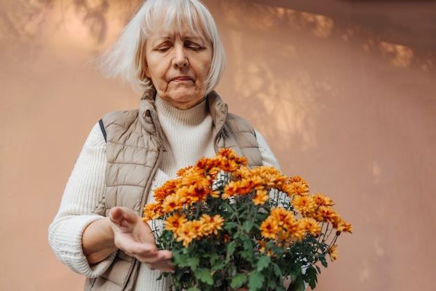 Mulher aposentada cuidando de flores decorativas em vasos.