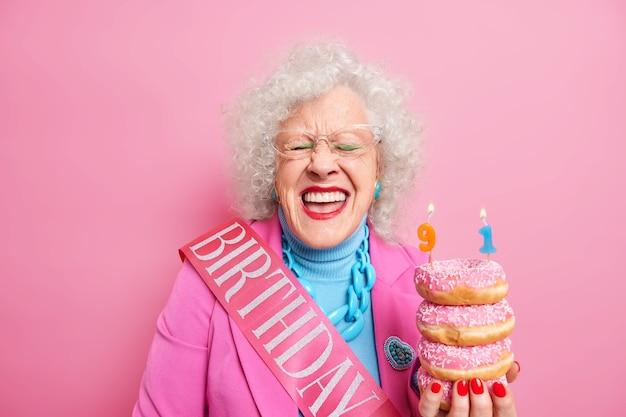 Mulher aposentada enrugada e radiante com sorrisos brilhantes de maquiagem segura uma pilha de donuts glaceados comemora 91º aniversário indo soprar velas usa traje rosa óculos transparentes poses dentro de casa