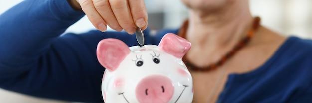 Mulher aposentada inserindo moeda no cofrinho rosa closeup