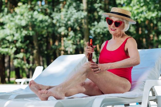 Mulher aposentada, loira e radiante, com lábios vermelhos e brilhantes, tomando banho de sol em um dia quente de verão