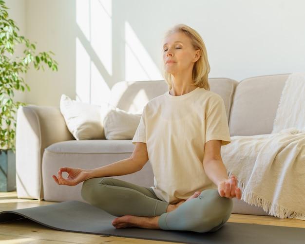 Mulher aposentada meditando e praticando ioga enquanto está sentada em posição de lótus no chão em casa