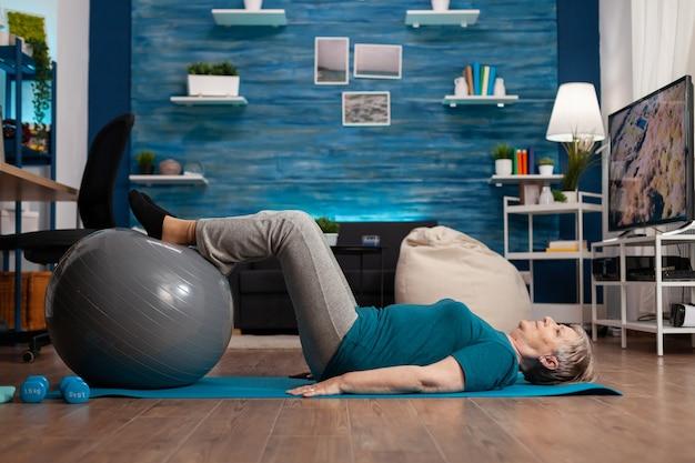 Mulher aposentada praticando exercícios com as pernas para cima, usando uma bola suíça, sentada em um tapete de ioga