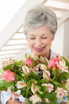 Mulher aposentada segurando buquê de flores e sorrindo