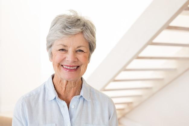 Mulher aposentada sorrindo para a câmera