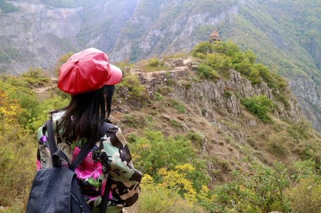 Mulher aprecia a vista deslumbrante do antigo pavilhão na montanha de goris, armênia