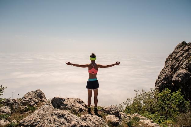 Mulher, apreciando a natureza nas montanhas e olhando no céu com as mãos levantadas.