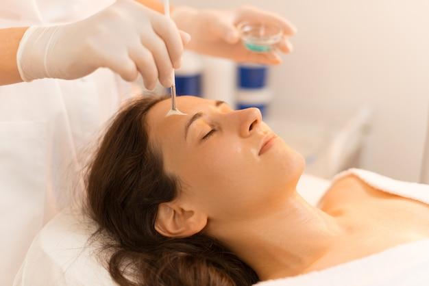 Mulher apreciando o procedimento e a máscara que o cosmetologista está aplicando com um pincel.