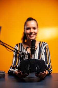 Mulher apresentando fone de ouvido vr para jogos em podcast