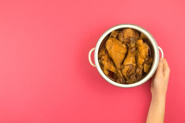 Mulher apresentando frango assado para um jantar em família, área de trabalho de cozinha minimalista e plano de fundo rosa plano, panela na mão, vista de cima e foto do espaço de cópia