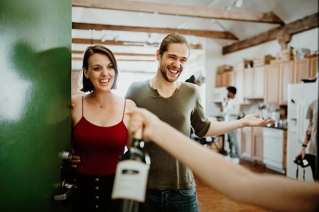 Mulher apresentando uma garrafa de vinho tinto Foto Premium