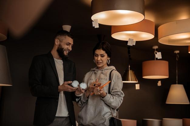 Mulher apresentando variante. casal muito bonito observando diferentes tamanhos de lâmpadas na seção de raios da loja