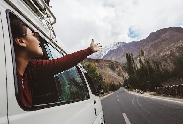 Mulher, aproveitando a brisa fresca da janela do carro