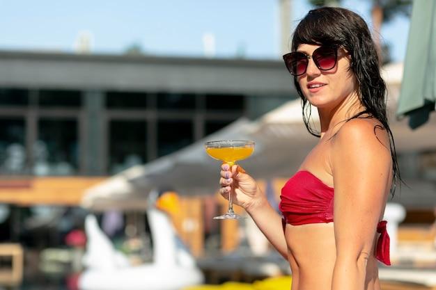 Mulher aproveitando o dia na piscina com coquetel