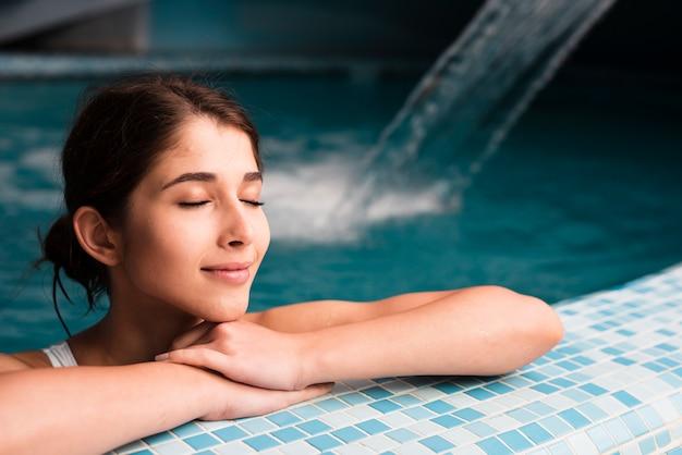 Mulher, aproveitando o dia relaxante na piscina no spa