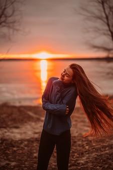 Mulher, aproveitando o tempo relaxante no lago bonito ao nascer do sol