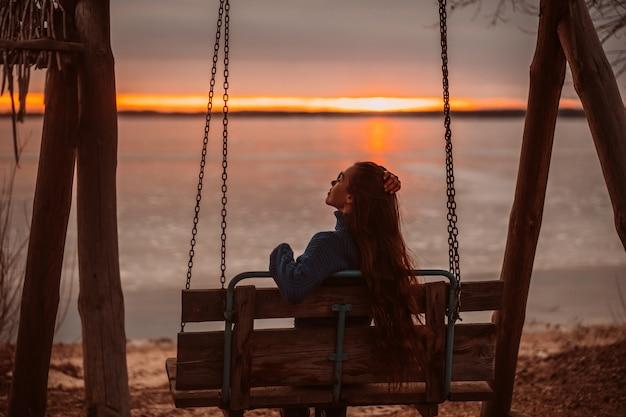 Mulher, aproveitando o tempo relaxante no lago bonito ao nascer do sol.