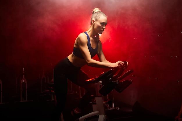 Mulher apta andando na bicicleta de fiação na academia, se exercitando sozinha, em uma sala enfumaçada com luzes de néon vermelhas