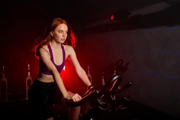 Mulher apta andando na bicicleta de fiação na academia, vestindo roupa esportiva, se exercitando sozinha, em um quarto enfumaçado com luzes de néon vermelhas