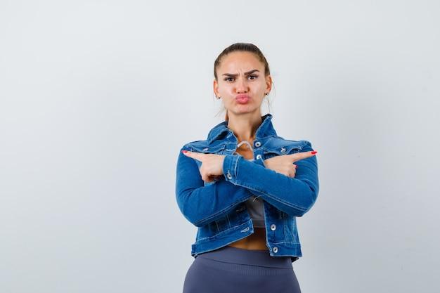 Mulher apta apontando direções opostas com os dedos indicadores, mandando beijos no top crop, jaqueta jeans, leggings e parecendo zangada. vista frontal.