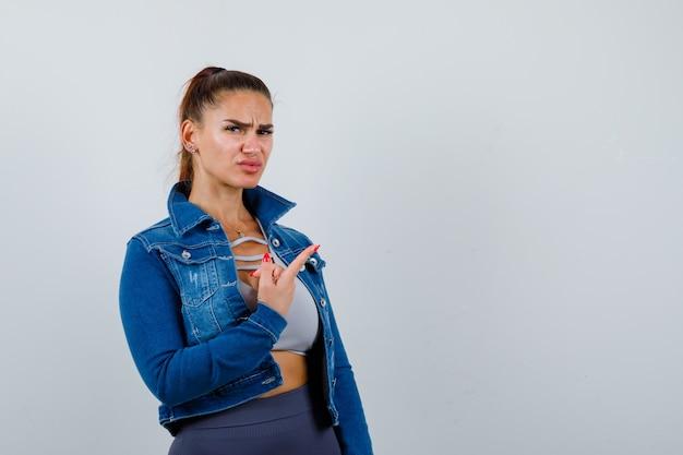 Mulher apta apontando para a direita com o dedo indicador, mandando beijos no top crop, jaqueta jeans, leggings e parecendo atormentada. vista frontal.