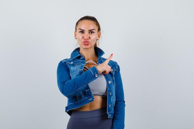Mulher apta apontando para a direita com o dedo indicador, mandando beijos no top crop, jaqueta jeans, leggings e parecendo fofa. vista frontal.