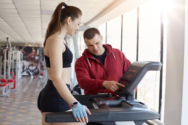 Mulher apta com rabo de cavalo, vestindo sutiã preto desportivo e curta sendo fotografada com treinador, definindo a velocidade para fazer jogging, garota fazendo exercícios físicos, fêmea gosta de fitness.