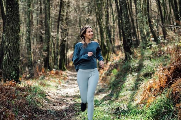 Mulher apta com roupa esportiva correndo ao longo da trilha na floresta verde