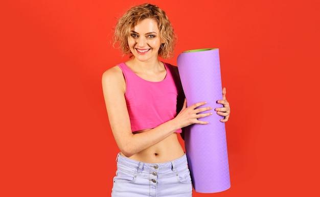 Mulher apta com tapete de ioga. desportista sorridente com tapete de fitness. estilo de vida saudável. garota esportiva.