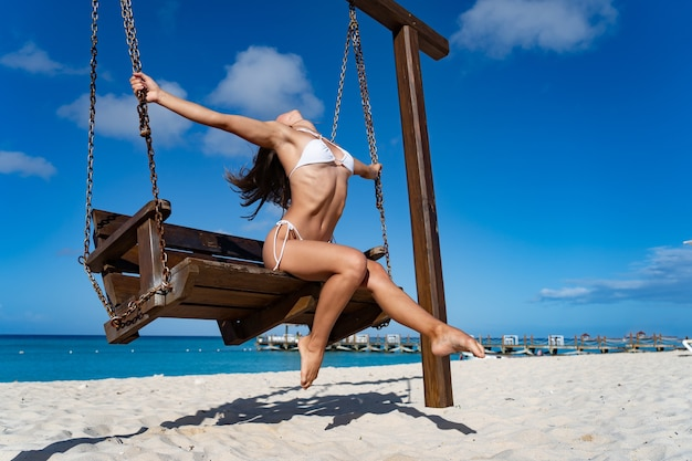 Mulher apta de biquíni branco sentada na praia e aproveite o banho de sol, a areia branca e a água do mar azul claro