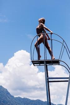 Mulher apta de biquíni na plataforma de mergulho, céu azul e nuvens