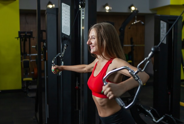 Mulher apta de sorriso flexionando os músculos na máquina de ginástica. menina executa exercícios com crossover de cabo de máquina de exercícios no ginásio moderno. fitness e musculação