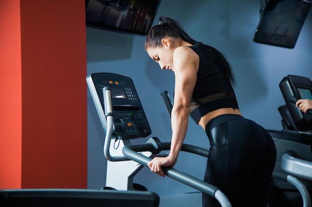 Mulher apta em máquina de cardio stepper na academia