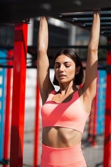 Mulher apta em roupa esportiva rosa ajustada ao ar livre pendurada na barra horizontal