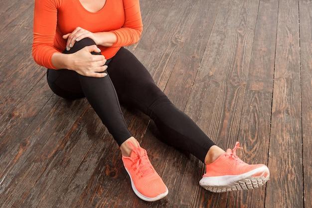 Mulher apta em roupas esportivas apertadas segurando um joelho dolorido sentado no chão no ginásio em casa, sofrendo de distensão muscular, entorse nos ligamentos ou lesão nas articulações, problemas de saúde após o treinamento esportivo. foto de estúdio interno