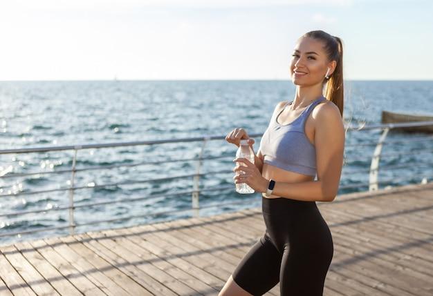 Mulher apta em roupas esportivas segurando uma garrafa de água na praia ao nascer do sol