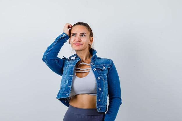 Mulher apta em top crop, jaqueta jeans, leggings coçando a cabeça, pensando em algo e parecendo pensativa, vista frontal.