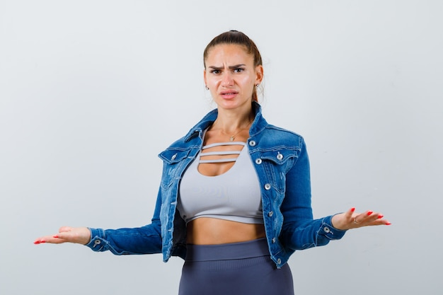 Mulher apta espalhando as palmas das mãos de uma maneira sem noção em top crop, jaqueta jeans, leggings e parecendo confusa. vista frontal.