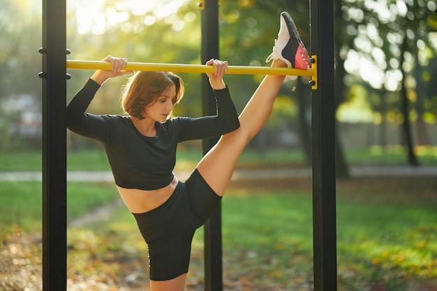 Mulher apta esticando as pernas na barra horizontal no parque