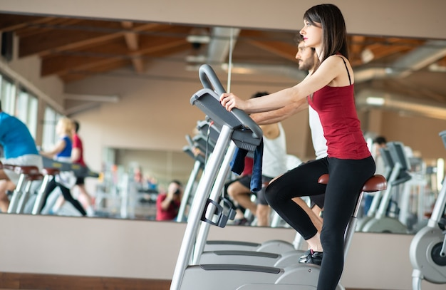 Mulher apta fazendo exercício em uma academia em uma bicicleta ergométrica