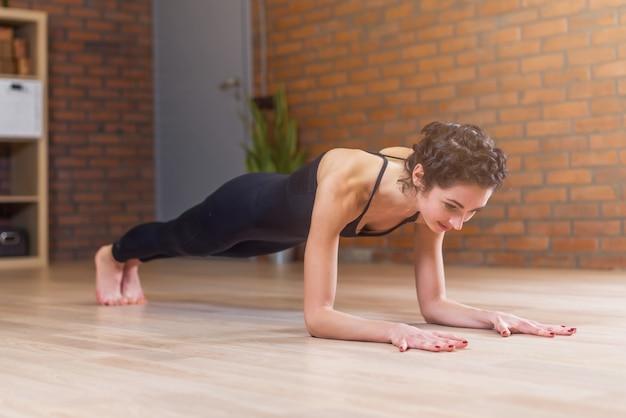 Mulher apta fazendo exercícios de ioga ou pilates em pé em uma pose de prancha chamada phalankasana, malhando no chão da sala de estar em casa
